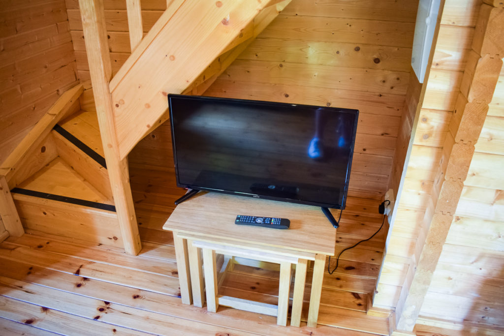TV on the table under the stairs in our 4 bed wooden villa lodge at la croix du vieux pont berny riviere