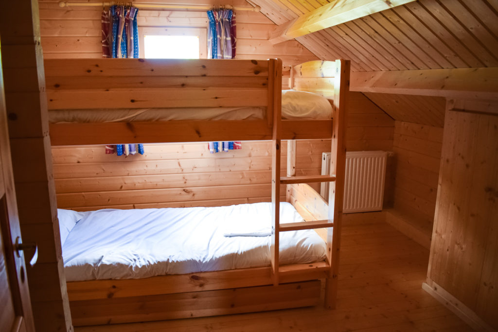Bunk bedroom with wooden bunk bed in the 4 bedroom villa lodge made out of wood at la croix du vieux pont berny riviere france with eurocamp