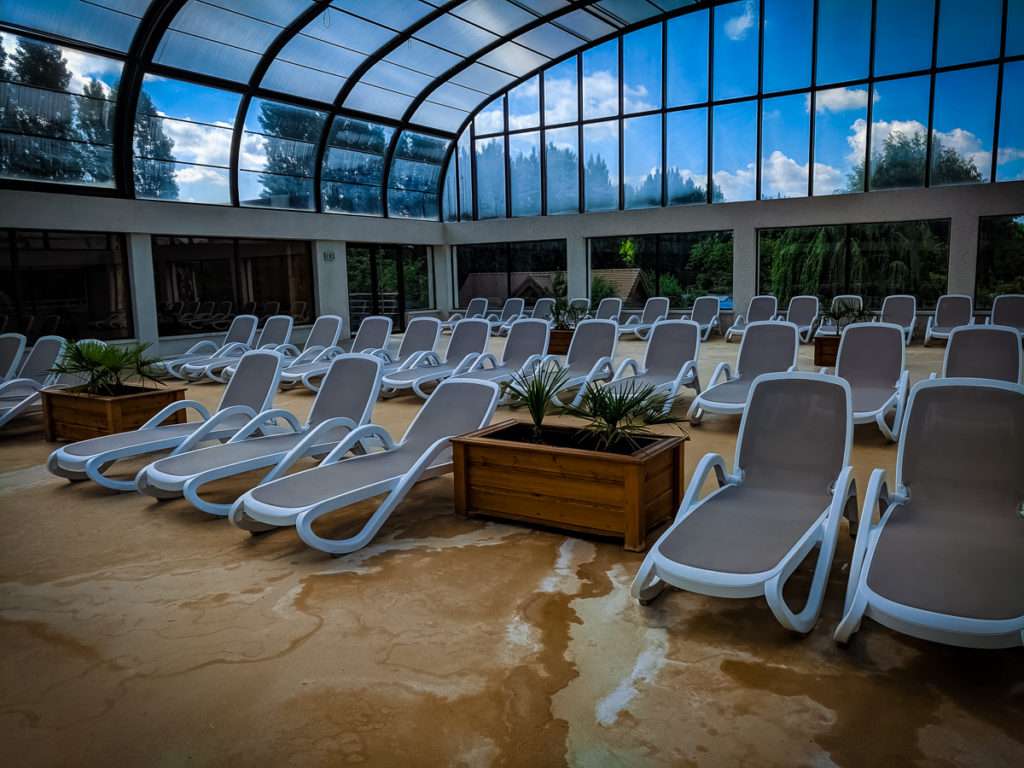 there are so many sun lounbgers inside at the pool area of camping La Croix du vieux pont berny riviere france (66)