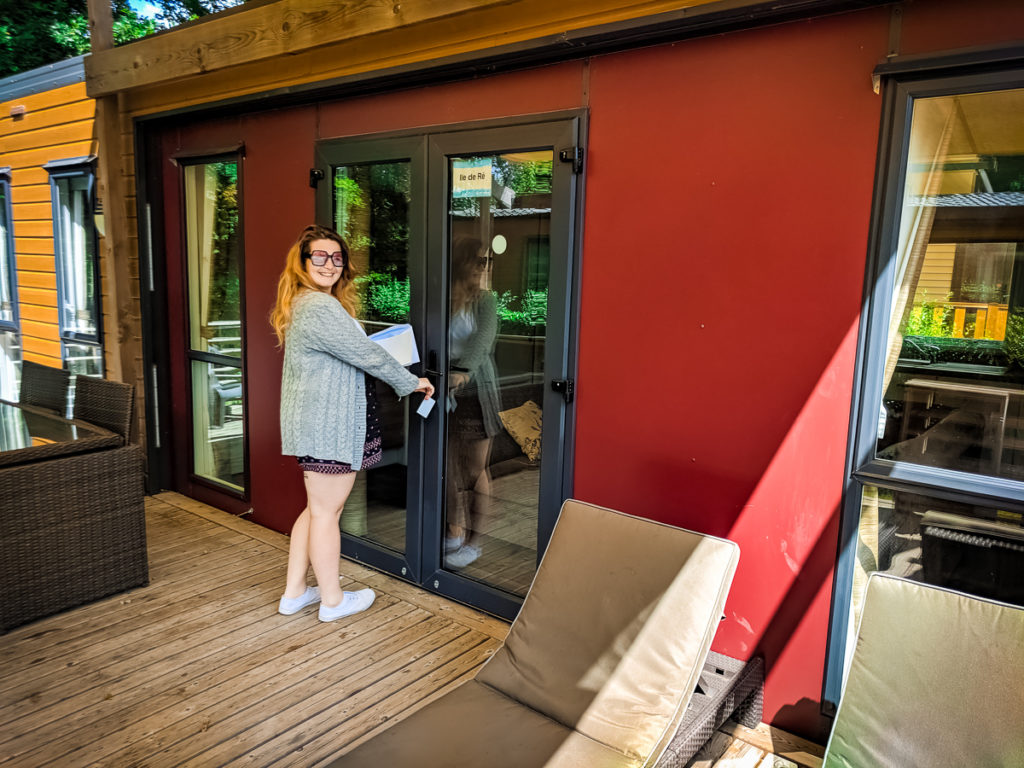 Breanne stood outside on the decking of the aspect mobile home by eurocamp at camping la garangeoire