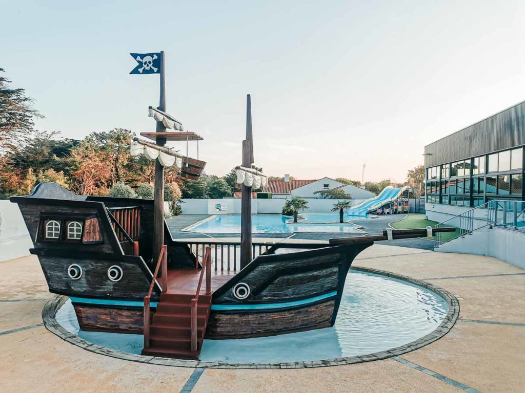Outdoor pool with a pirate ship play area at Camping de l'ocean Brem Sur Mer