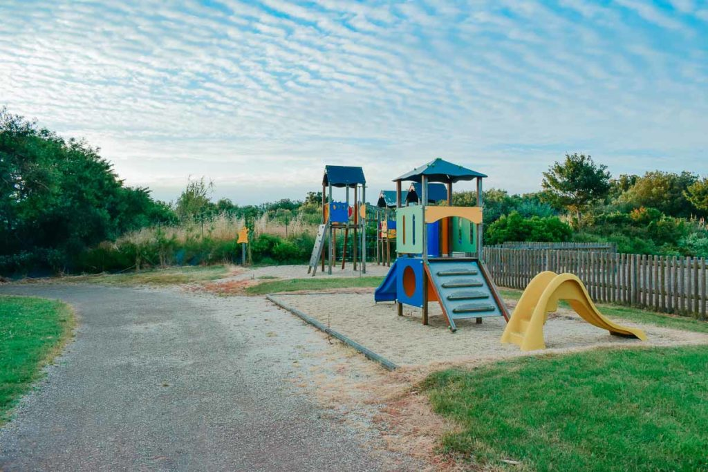 Play park with climbing frame and kids yellow slide at Camping de l'ocean Brem Sur Mer