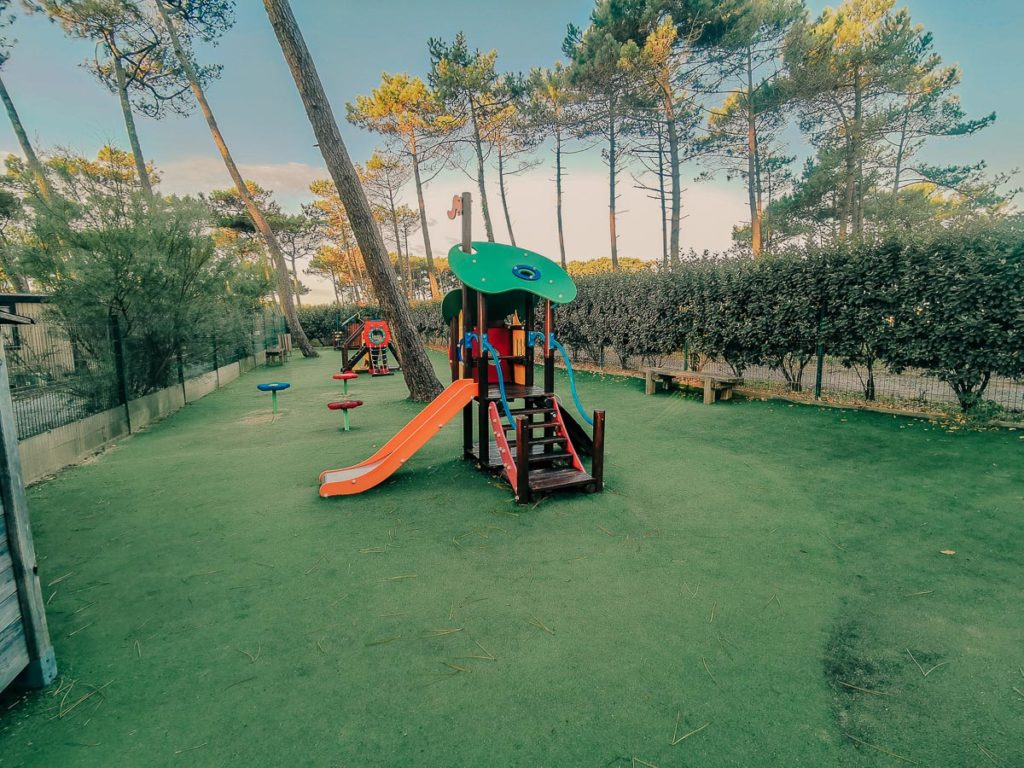 The astroturffed kids play park with view of pine trees in background at camping le vieux port by Resasol in Messanges, Landes department, France