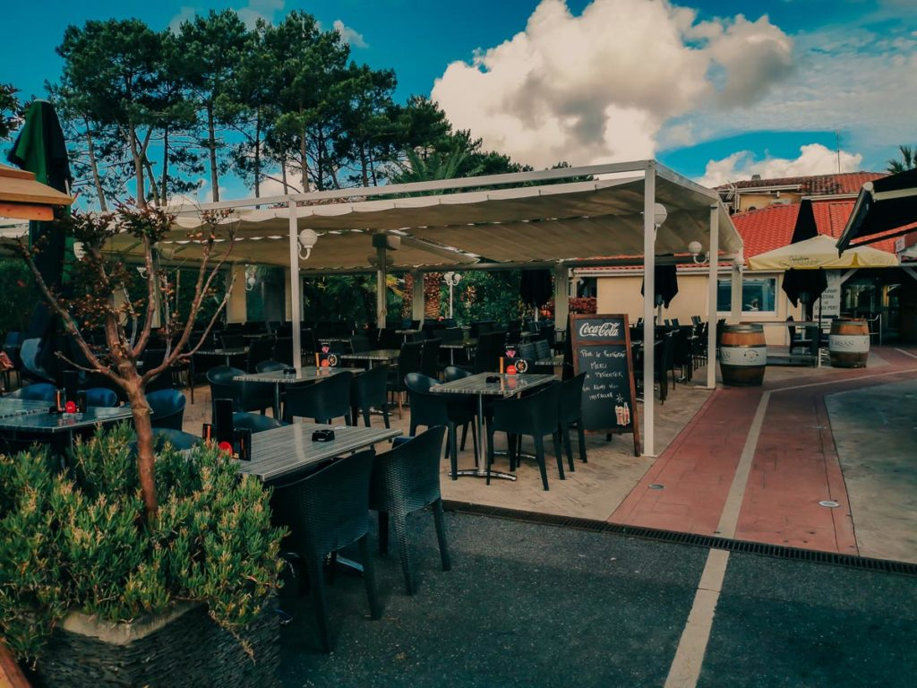 seating area with tables and chairs with covered canopy in the restaurant at camping le vieux port by Resasol in Messanges, Landes department, France