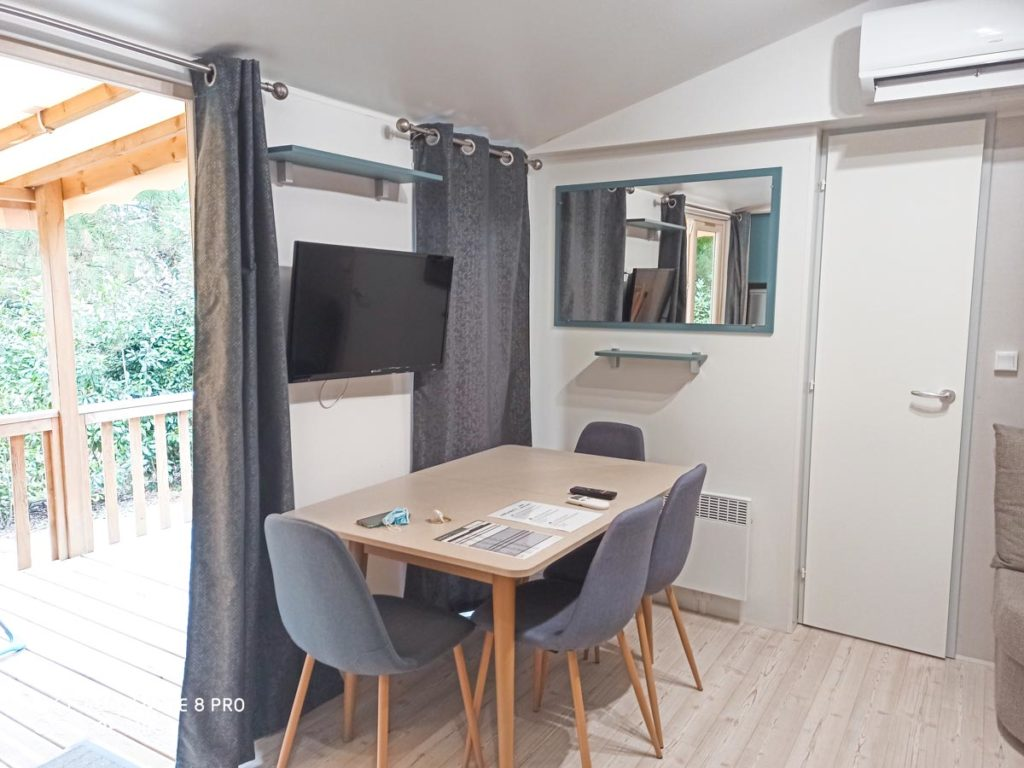 Dining table with TV in our premium cottage at camping natureo in hossegor-09