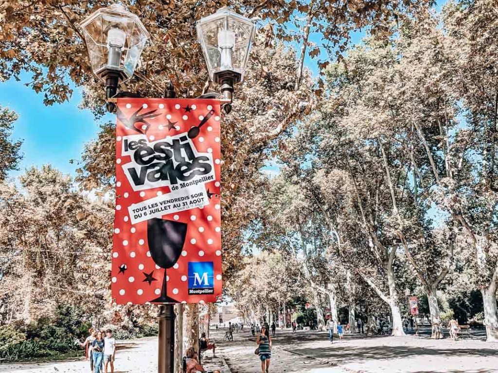 A sign about the estivales in charles de gaulle esplanade a location in montpellier. photo of signs, lamps and trees