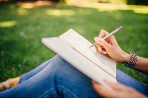 an image of a person sat down on green grass writing how to plan the best camping trip in a notebook