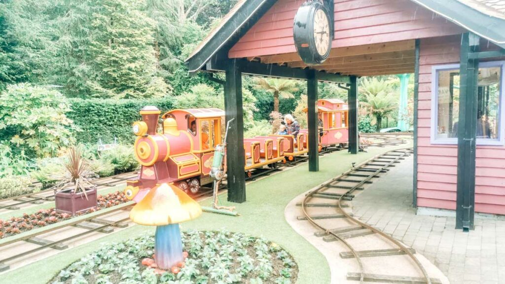 the train in critter creek with the toddler and her nanny riding in the middle seats at Paultons-park-and-peppa-pig-world