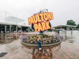 the toddler in front of the paultons park sign in the rain