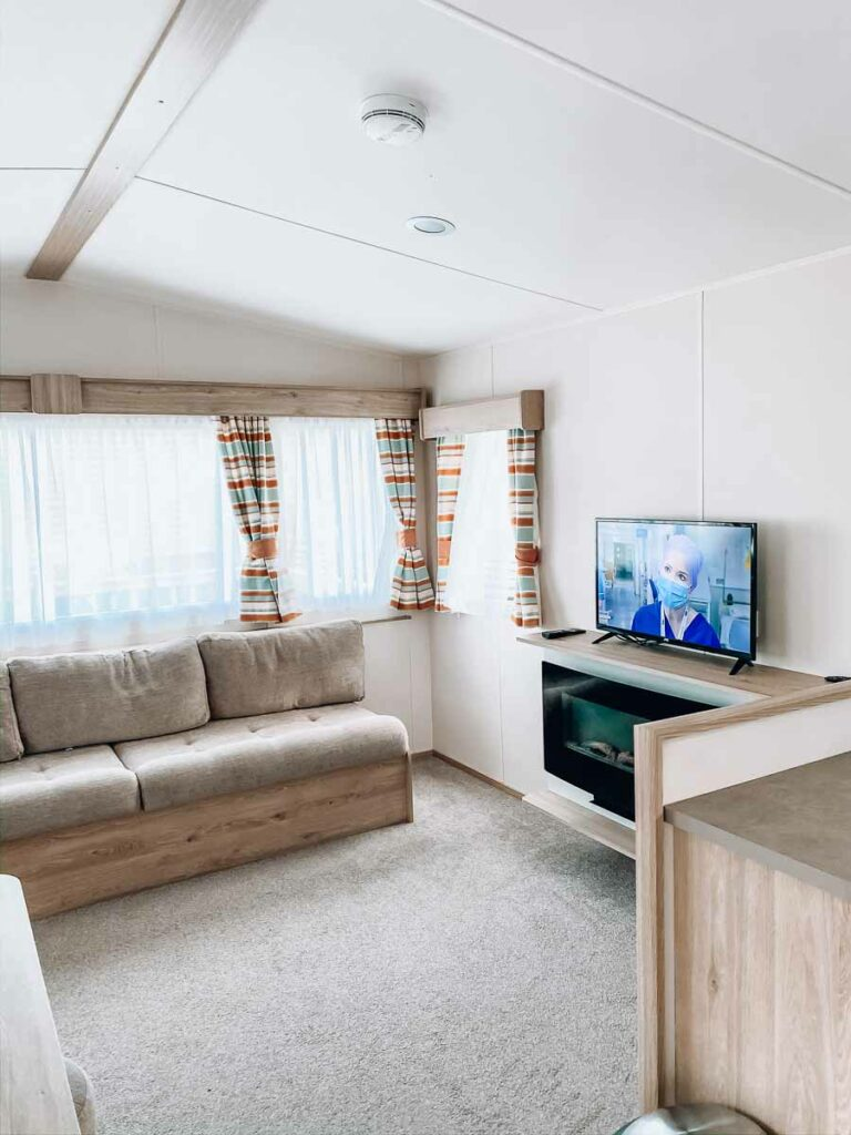 main-living-area-with-TV-and-fireplace-in-our-classic-caravan-at-Hoburne-holiday-bashley-holiday-park