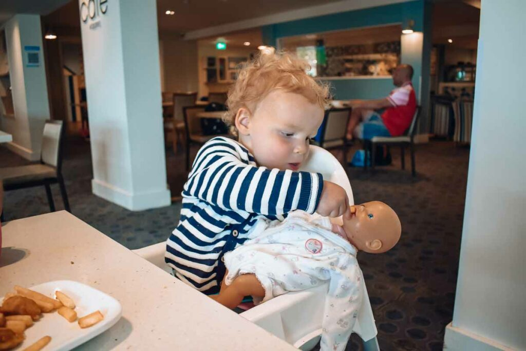toddler-feeding-her-baby-doll-at-the-bar-area-in-hoburne-bashley-park-campsite