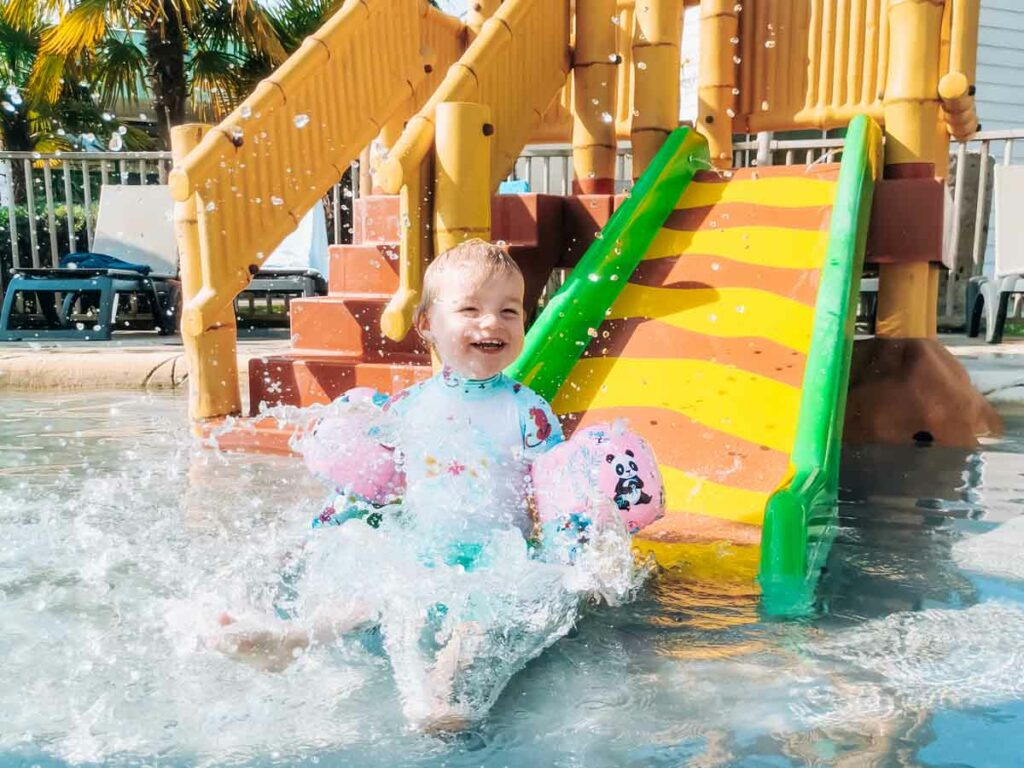 toddler on the kids water slide at camping la roche posay yelloh village campsite